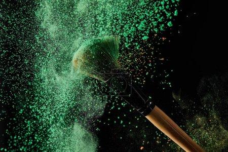 Foto de Cepillo cosmético con explosión de polvo verde sobre fondo negro - Imagen libre de derechos
