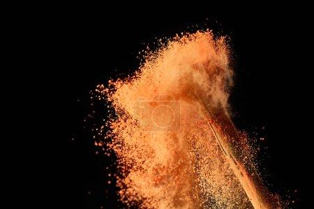 Foto de Cepillo cosmético con explosión de pintura colorida sobre fondo negro - Imagen libre de derechos