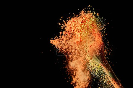 Foto de Cepillo cosmético con explosión de pintura naranja sobre fondo negro con espacio de copia - Imagen libre de derechos