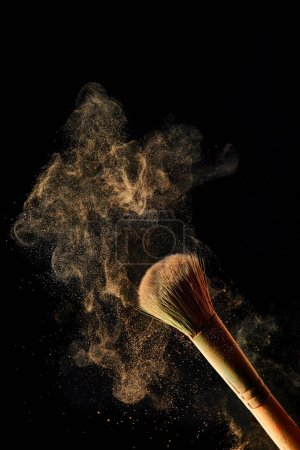 Foto de Cepillo cosmético con polvo de luz de colores sobre fondo negro - Imagen libre de derechos