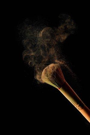 Foto de Cepillo cosmético con polvo ligero sobre fondo negro - Imagen libre de derechos