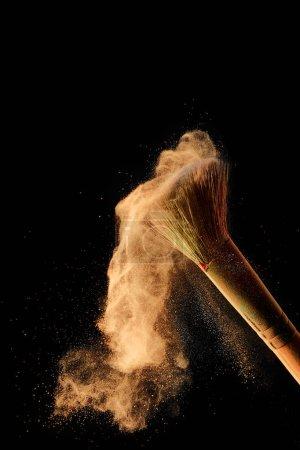 Photo pour Pinceau cosmétique avec poudre orange dispersée sur fond noir - image libre de droit