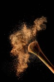 "Постер, картина, фотообои ""cosmetic brush with colorful orange powder cloud on black background"""
