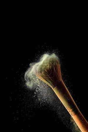 Foto de Cepillo cosmético con polvo de dispersión de colores amarillos sobre fondo negro - Imagen libre de derechos