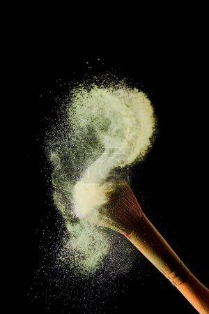 Photo pour Brosse cosmétique avec la poussière dispersée colorée jaune sur le fond noir - image libre de droit