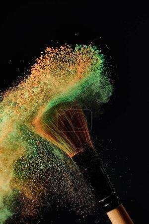 Photo pour Brosse cosmétique avec explosion de poudre verte et orange sur fond noir - image libre de droit