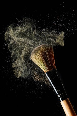 Photo pour Brosse cosmétique avec la poussière légère jaune sur le fond noir - image libre de droit