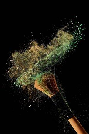Foto de Cepillo cosmético con polvo verde y naranja sobre fondo negro - Imagen libre de derechos