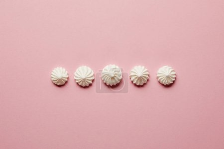 Photo for Flat lay with sweet white meringues in horizontal row on pink background - Royalty Free Image