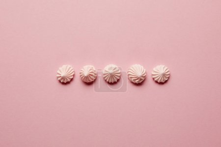 Photo for Flat lay with pink meringues in horizontal row on pink background - Royalty Free Image
