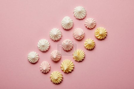 Photo for Top view of white, pink and yellow meringues in rows on pink background - Royalty Free Image