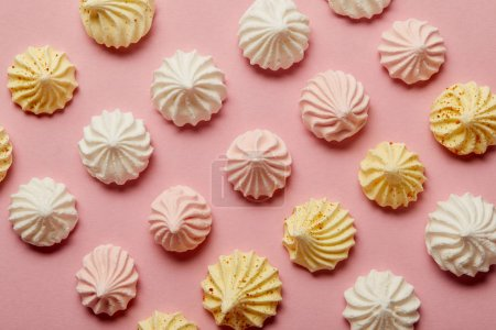 Photo for Flat lay with white, pink and yellow meringues on pink background - Royalty Free Image