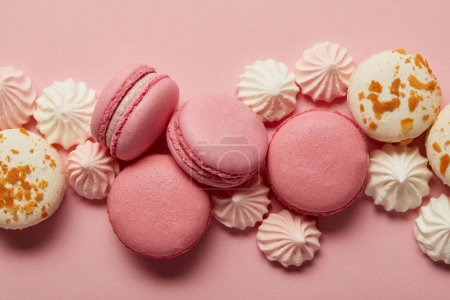 Photo for Pink and white tasty macaroons with pink and white meringues on pink background - Royalty Free Image