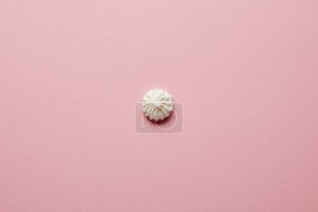 Photo for Top view of small white meringue in center on pink background - Royalty Free Image
