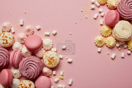 Photo for Top view of delicious sweet macaroons, meringues and marshmallows with yellow pieces on pink background - Royalty Free Image
