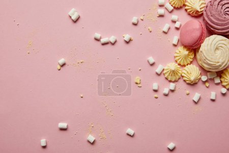 Photo for Top view of sweet pink macaroons, meringues and marshmallows with yellow pieces on pink background - Royalty Free Image