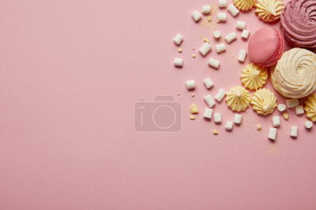 Photo for Top view of pink sweet macaroons, yellow meringues and marshmallows on pink background - Royalty Free Image