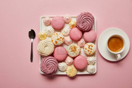 Photo for Flat lay with assorted meringues and macaroons on square dish with cup of coffee and spoon on pink background - Royalty Free Image