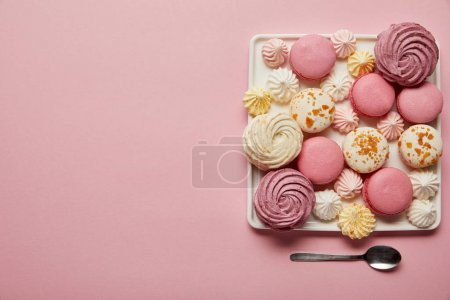 Photo for Flat lay with assorted meringues and macaroons on square dish with spoon on pink background - Royalty Free Image