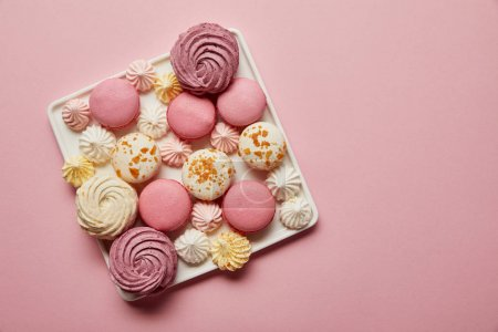 Photo for Top view of assorted french macaroons and meringues on square dish on pink background - Royalty Free Image