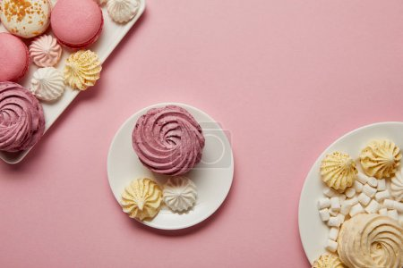 Photo for Soft pink zephyr with small meringues on saucer with macaroons and marshmallows on plates on pink background - Royalty Free Image