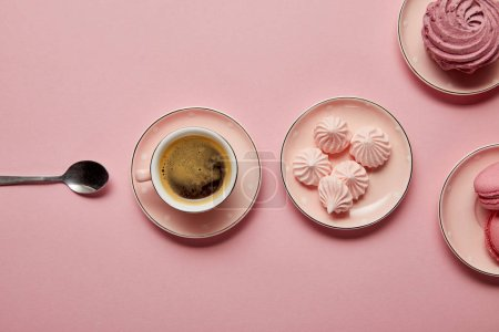 Foto de Top view of pink meringues and macaroons on pink dotted saucers with spoon and cup of coffee on pink background - Imagen libre de derechos