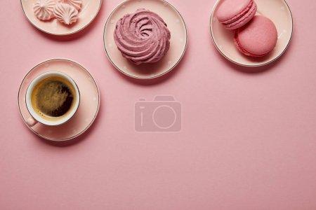 Photo pour Vue supérieure des meringues roses, des macarons et de la tasse de café sur les soucoupes roses avec des points blancs sur le fond rose - image libre de droit