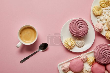 Foto de Vista superior de merenmos rosas, blancos y amarillos, macarrones, malvaviscos y taza de café con cuchara sobre fondo rosa - Imagen libre de derechos