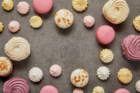 Photo for Top view of pink and white macaroons with meringues on gray background - Royalty Free Image