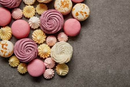 Photo for Top view of assorted delicious french macaroons with meringues on gray background - Royalty Free Image
