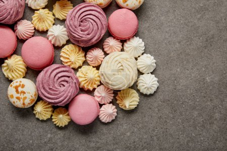Photo for Top view of meringues, macaroons and fluffy white and pink zephyr on gray background - Royalty Free Image