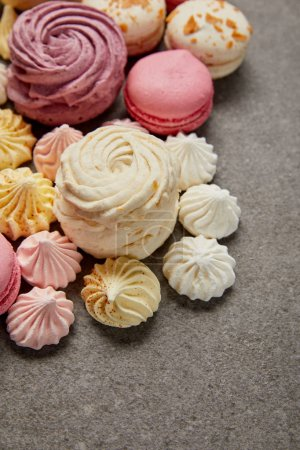 Photo for Delicious assorted soft zephyr, small meringues and macaroons on gray background - Royalty Free Image