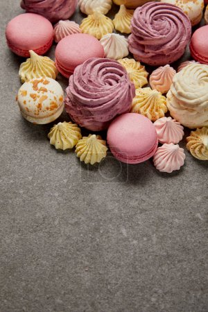 Photo for Tasty assorted small meringues, soft zephyr with french macaroons on gray background - Royalty Free Image