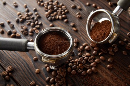 Photo for Portafilters with aromatic fresh coffee on dark wooden surface with coffee beans - Royalty Free Image
