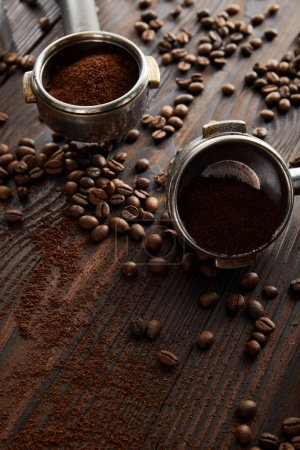 Photo for Portafilters filled with aromatic ground coffee on dark wooden surface with coffee beans - Royalty Free Image