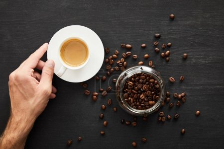 Photo for Top view of male hand with cup of coffee near glass jar with coffee beans - Royalty Free Image