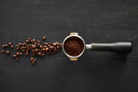 Photo for Top view of portafilter with coffee on dark wooden surface with scattered coffee beans - Royalty Free Image