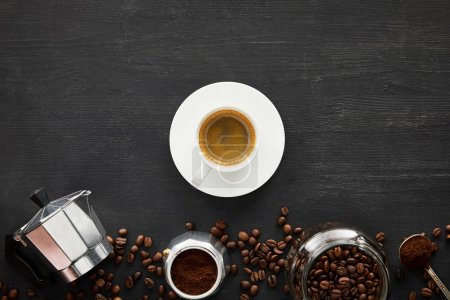 Photo for Top view of cup of espresso on saucer near geyser coffee maker, glass jar and spoon on dark wooden surface with coffee beans - Royalty Free Image
