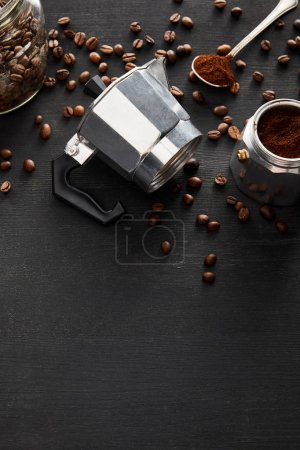 Photo for Separated parts of geyser coffee maker near glass jar and spoon on dark wooden surface with coffee beans - Royalty Free Image
