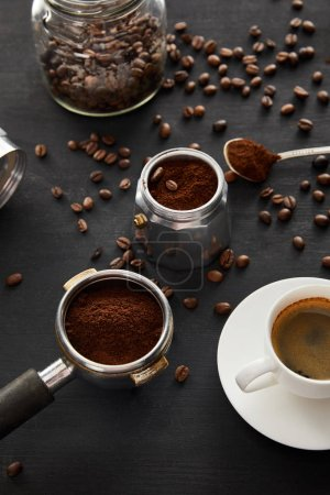 Photo for Geyser coffee maker near cup of coffee, portafilter, spoon and glass jar on dark wooden surface with coffee beans - Royalty Free Image