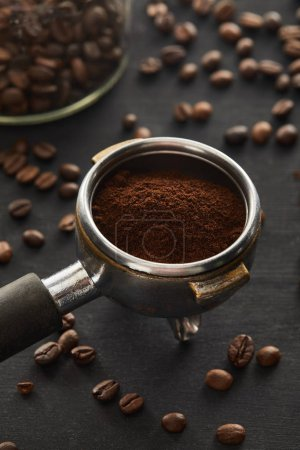 Photo for Portafilter filled with ground coffee near glass jar on dark wooden surface - Royalty Free Image