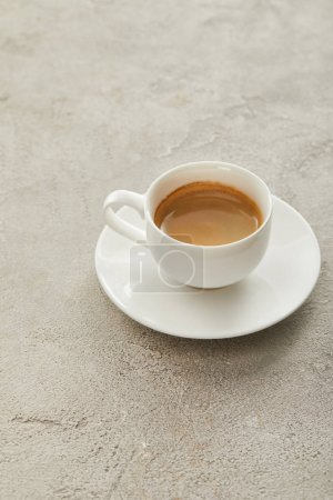 White cup with coffee on saucer on light marble surface