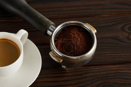 Photo for Portafilter with fresh ground coffee near cup of espresso on dark wooden surface - Royalty Free Image
