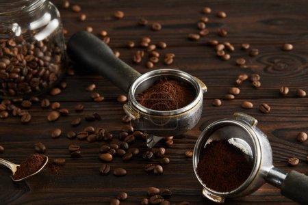 Photo pour Portafilters près geyser pot en verre avec café et cuillère sur la surface en bois sombre - image libre de droit