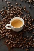 """Постер, картина, фотообои """"Белая чашка с кофе на темной поверхности с разбросанными кофейными зернами"""""""