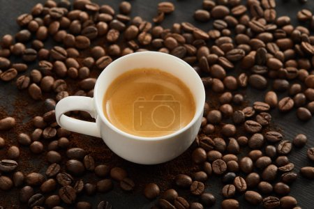 Photo for White ceramic cup with espresso on surface with scattered coffee beans - Royalty Free Image