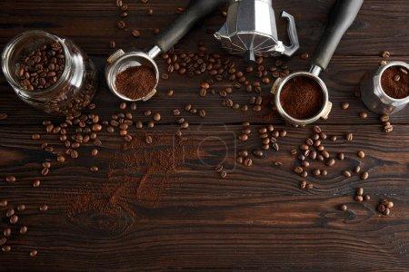 Photo pour Vue du dessus du bocal en verre près de la cafetière geyser et des portafilters sur une surface en bois sombre avec des grains de café - image libre de droit