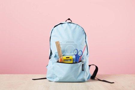 Photo pour Sac à dos bleu d'école avec la papeterie dans la poche d'isolement sur le rose - image libre de droit