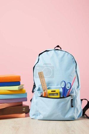 Foto de School blue backpack with supplies in pocket near stack of books isolated on pink - Imagen libre de derechos