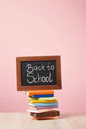 Photo for Stack of books with chalkboard with back to school lettering isolated on pink - Royalty Free Image